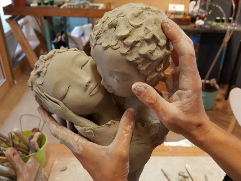 Lydie Thonnerieux sculptant deux personnages, zoom sur ses mains elle modèle deux visages