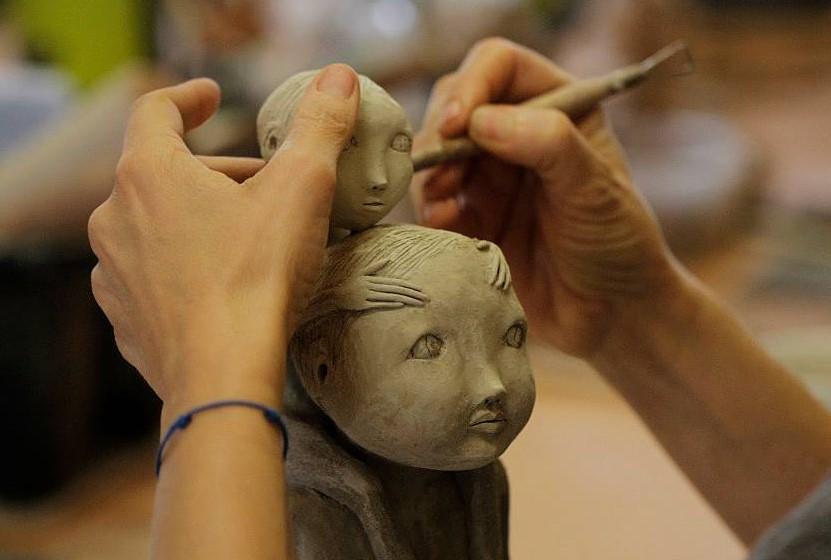 Lydie Thonnerieux sculptant deux personnages, zoom sur ses mains sculptants deux visages