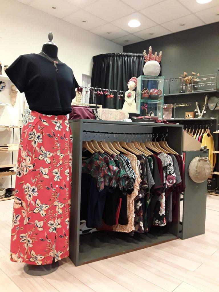 Intérieur de la boutique en ligne, mannequin avec une jupe rouge à fleur et un tshirt bleu avec un collier doré. Présentoirs avec de nombreuses créations, bijoux, céramique, vêtements